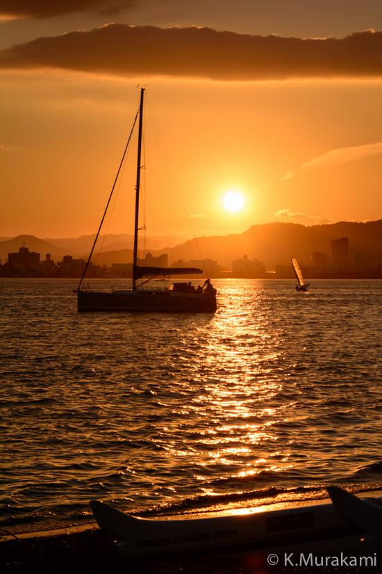 夕日に輝く海面とヨット